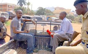 Daily Monitor journalists on a police patrol car