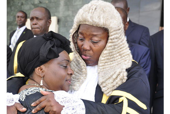 Speaker Rebecca Kadaga comforts Gender minister Mary Karooro Okurut at Parliament yesterday. This was during a special session to honour the minister's late husband Stanislaus Okurut.  PHOTO BY GEOFFREY SSERUYANGE