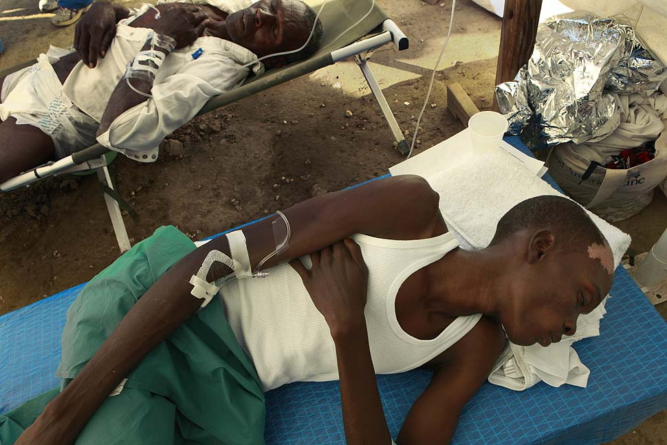 Two men suffering from cholera rest while receiving treatment at an emergency cholera clinic run by Samaritan's Purse outside of Cabaret, Haiti. Despite the work of aid organization, over 89,000 have been infected so far.